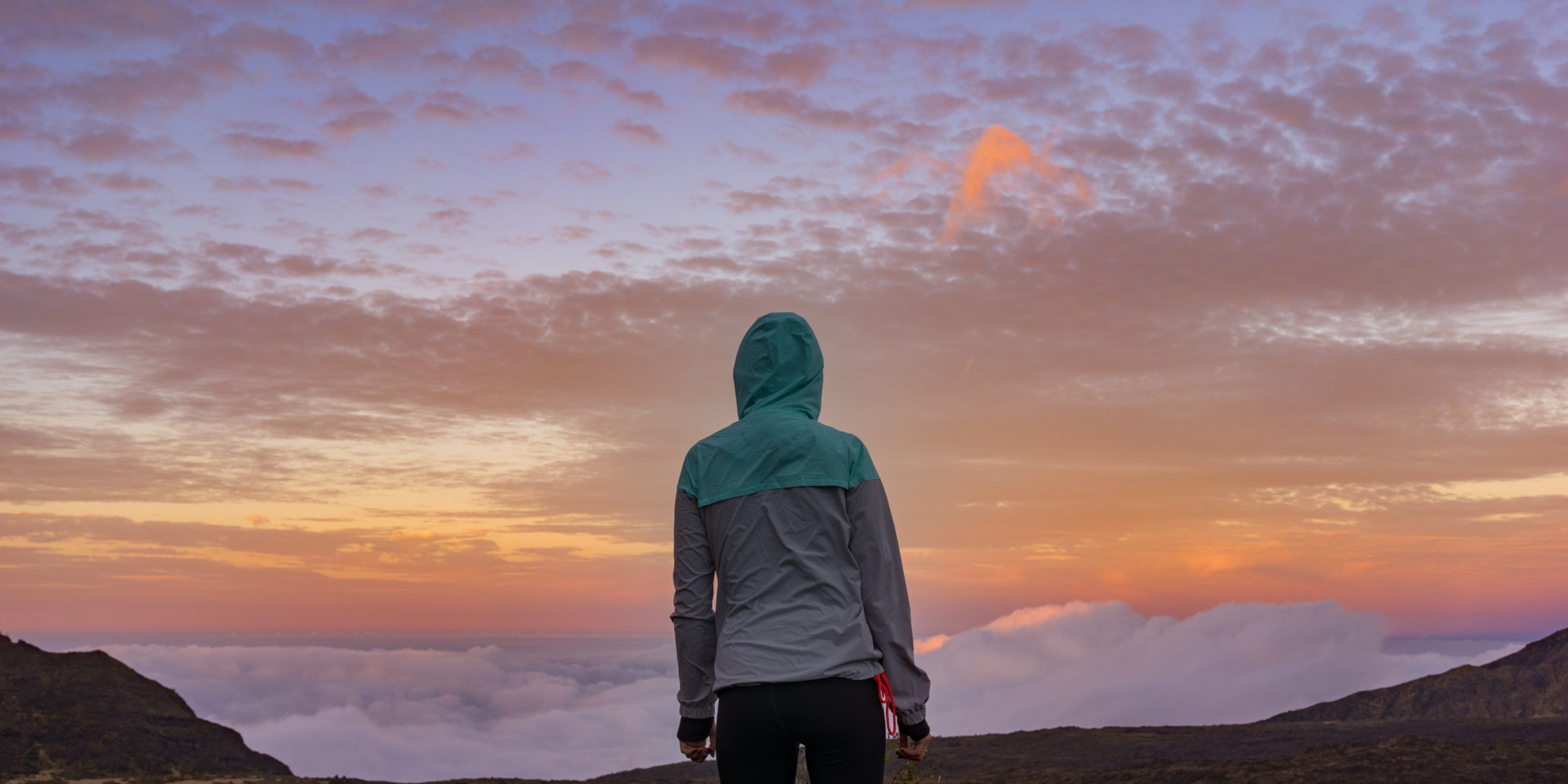 ed_young-woman-standing-on-a-mountain-looking-over-the-clouds